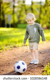 Little boy having fun playing a soccer game on sunny summer day. Active outdoors game for toddler and family with kids