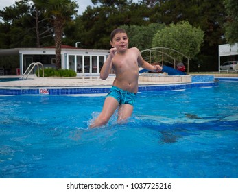 Little boy having fun playing in the pool, jumping and water splashing during summer vacation on the seaside.