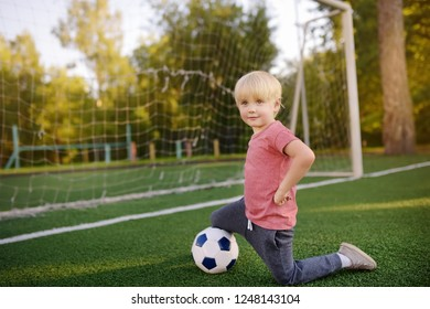Little boy having fun playing a soccer/football game on summer day. Active outdoors game/sport for children. Kids soccer classes and camps