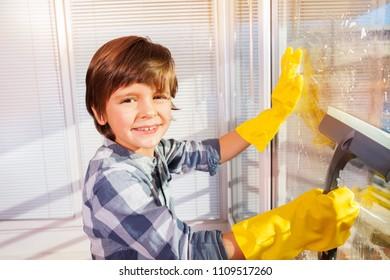 Little boy having fun washing windows at home