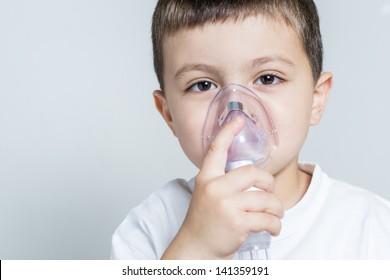 Little boy having inhalation for easing cough.