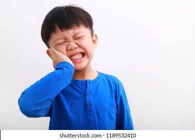 Little boy having toothache. Emotional portrait of asian boy suffering. Sad child with tooth pain. Dental problem - kid suffering from toothache.