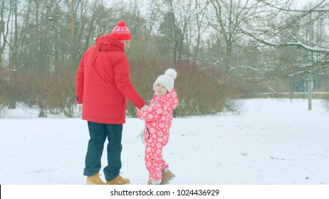 Little boy are having a walk with his grandfather in the winter park