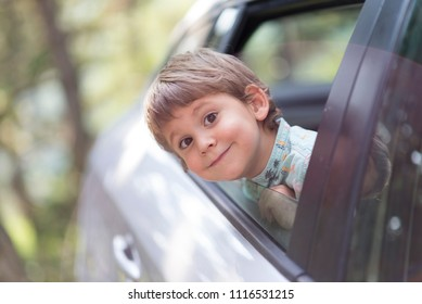 little boy with head leaned through the open window of a car