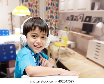 Little boy with headset doing homework in the room