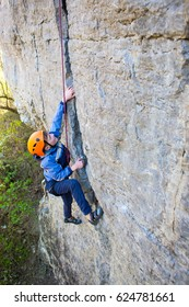 The little boy in the helmet climbs the rock, kid rock climber sports outdoors.