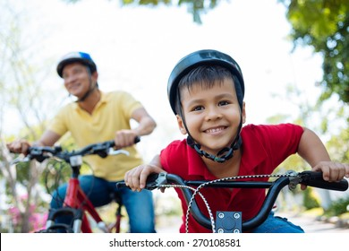 Little boy in helmet enjoying riding a bicycle