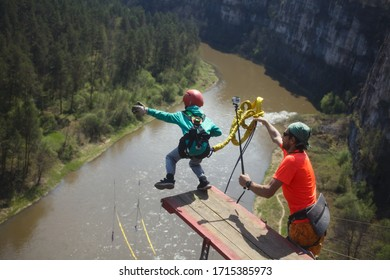 Little boy, in a helmet, fixed on a safety rope, jumps down from a wooden platform into a deep canyon, next to him is a male assistant, rear view. Ropejumping - sports jumping with a rope.