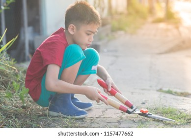 Little boy help to cut grass on the street
