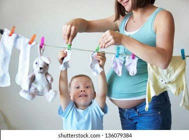 Little boy helping hang laundry his pregnant mother