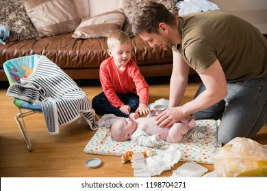 Little boy helping his father change his baby brother. They are both sitting on the floor in the living room.