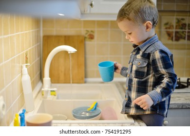 little boy helping mother washing dishes in the kitchen