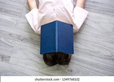 Little boy hide face with open book laying in floor. Child sleep with story book on face