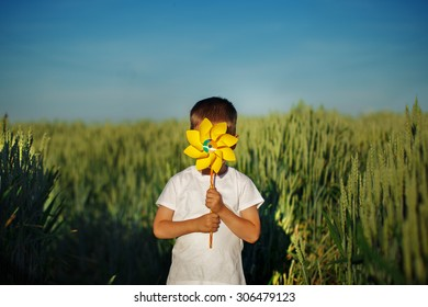 Little boy hides behind yellow pinwheel on blue sky and green field background