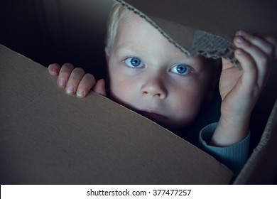 Little boy hiding in box