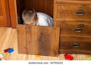 Little boy is hiding in the cupboard in the playroom