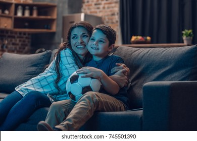 Little boy and his beautiful mother hugging on couch while watching a soccer game