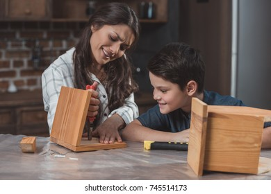 Little boy  and his beautiful mother crafting a wooden birdhouse at home
