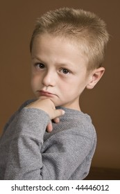 Little boy with his chin on his hand.
