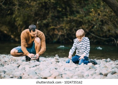 Little boy and his father are building cairns on the beach.