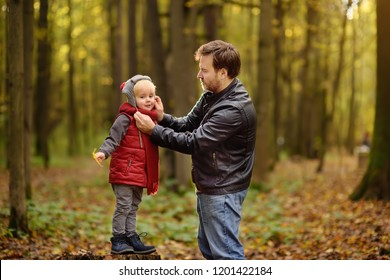Little boy with his father during stroll in the forest. Active family time on nature. Fun with little kids in fall days