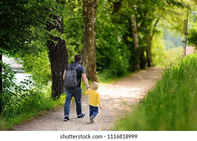 Little boy and his father enjoying warm summer day. Parent and pupil going to kindergarten of preschool. Active family walking in park. Rest and childhood concept. Parent and pupil going to kindergart