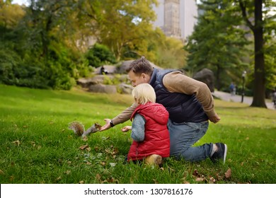 Little boy with his father feeding squirrel in central park, Manhattan, New York. Wild animals in the city. Quality family time.