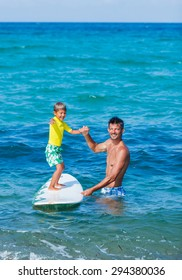 Little boy with his father learning surfing