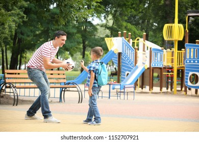 Little boy with his father playing football outdoors