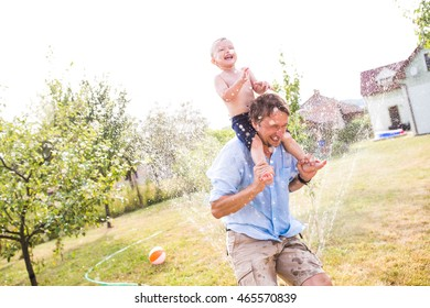 Little boy with his father at the sprinkler, summer
