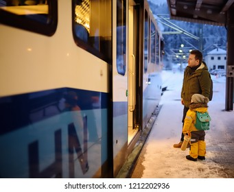 A little boy with his father take the funicular train to the top Zugspitze mountain. Travelling with children concepts.