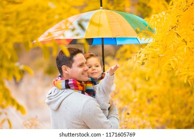 A little boy and his father are under a colorful umbrella. Family in warm clothes and colorful scarves. the kid catches the rain drops with his palm