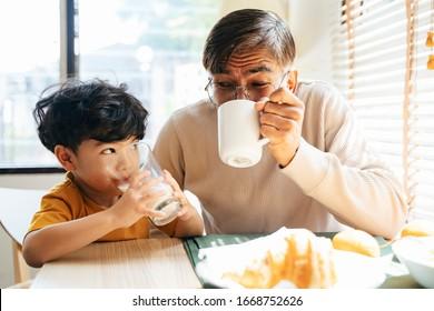 Der kleine Junge und sein Großvater trinken das Getränk zusammen, er trinkt die Milch, während sein Großvater den Kaffee am Morgen trinkt.