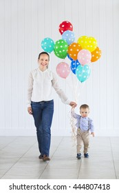 Little boy with his mom holding a large bunch of colored balloons