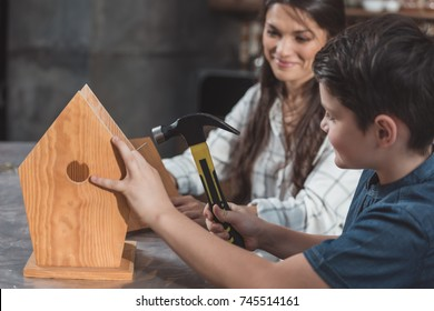 Little boy and his mother building a wooden birdhouse with hammer