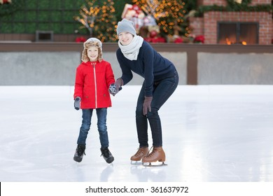little boy and his mother ice skating together at outdoor skating rink with holiday decorations, having winter vacation fun