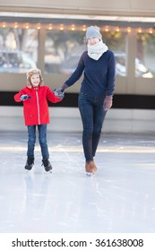 little boy and his mother ice skating together at outdoor skating rink, having winter vacation fun