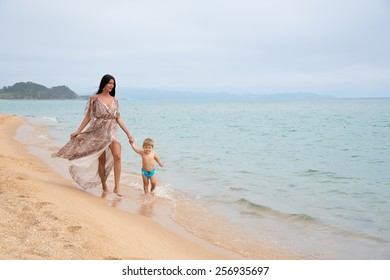 Little boy and his mother on the beach on a summer day.
