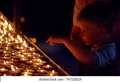 a little boy with his mother put a candle in a holy place