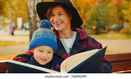 Little boy and his mother are reading book in the autumn park
