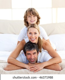 Little boy and his parents playing lying on the bed