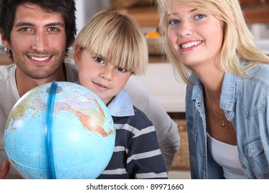 a little boy and his parents smiling near a globe