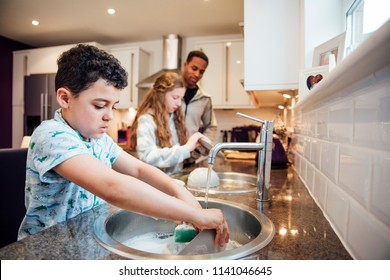 Little boy and his sister are helping dad with the washing up at home.