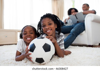 Little boy and his sister holding soccer ball lying on the floor