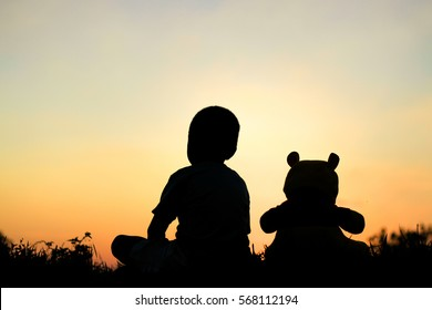 little boy with his teddy bear friend on sunset. concept of lonely.
