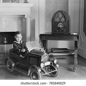 Little boy in his toy automobile next to a state of the art Atwater Kent Radio. The radio features enclosed speakers behind the fabric covered openings in the refined cabinet