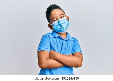 Little boy hispanic kid wearing medical mask happy face smiling with crossed arms looking at the camera. positive person.