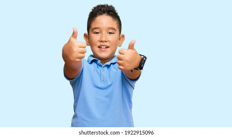 Little boy hispanic kid wearing casual clothes success sign doing positive gesture with hand, thumbs up smiling and happy. cheerful expression and winner gesture.