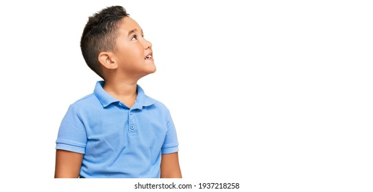Little boy hispanic kid wearing casual clothes looking away to side with smile on face, natural expression. laughing confident.