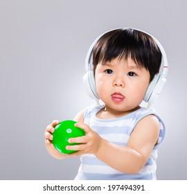 Little boy hold ball and wear headphone